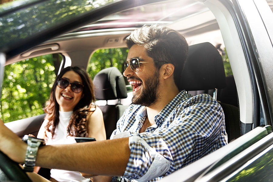 Insurance Quote - Young Couple Enjoying Their Car Ride on Sunny Day